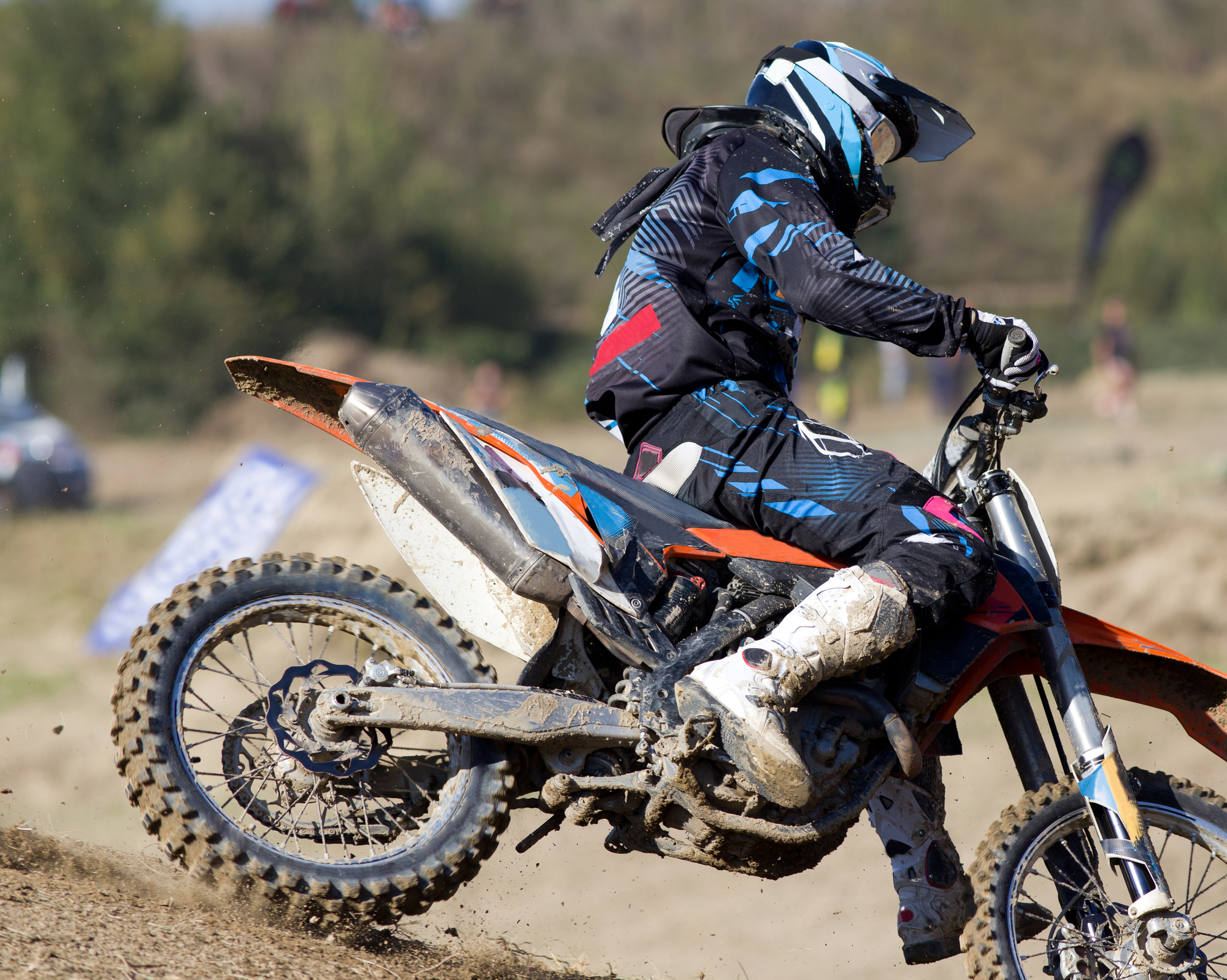 Biker riding motorcycle in mud at off road race